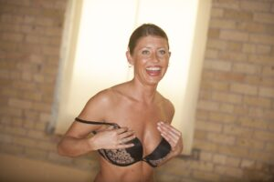 Woman smiling putting bra on after Houston breast lift for perkier breasts
